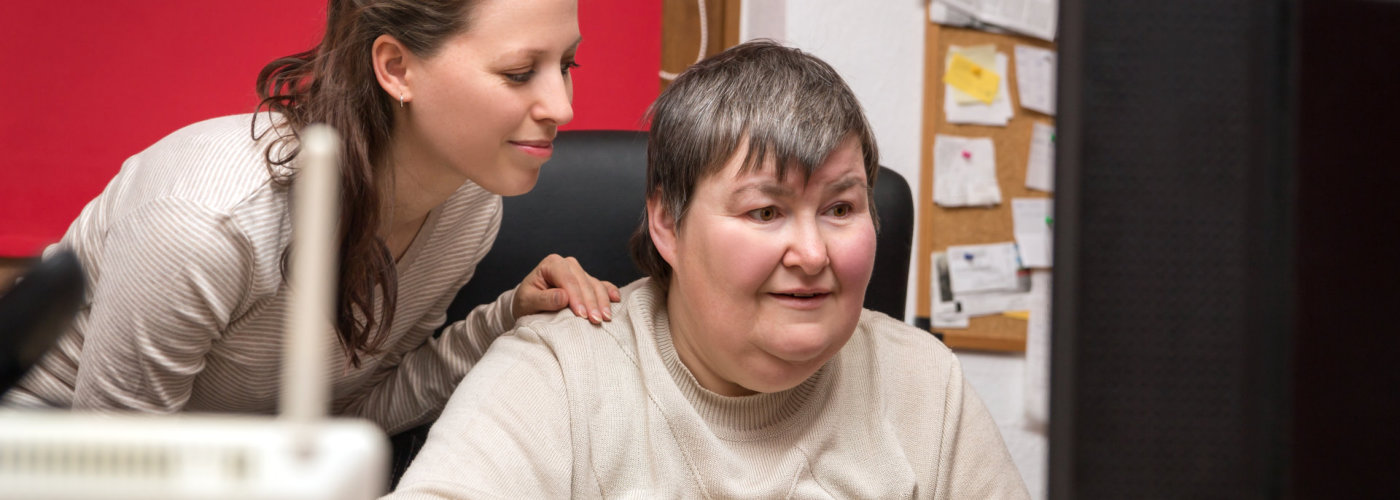 caregiver teaching mentally disabled woman